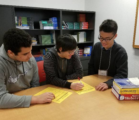 Students get help for a class requirement with a tutor.