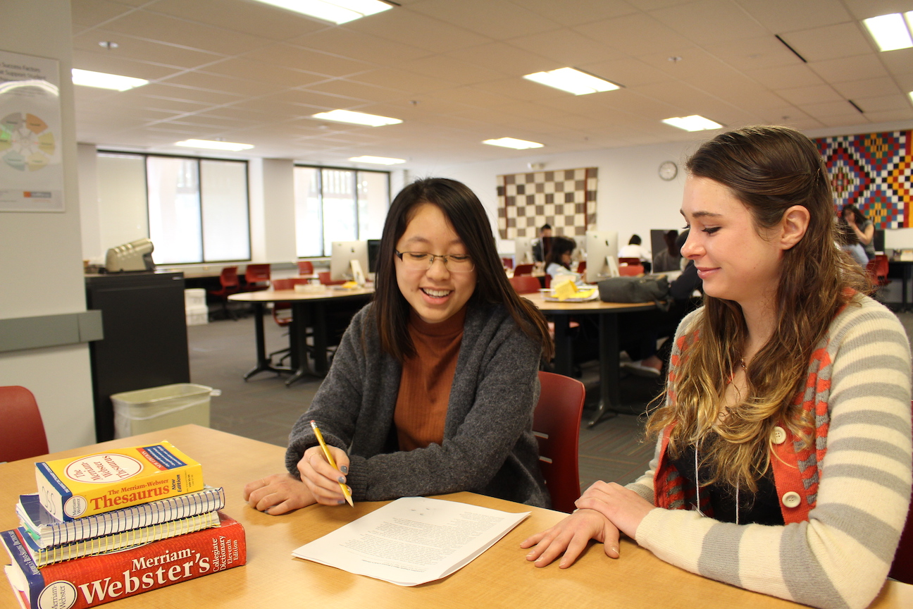 A tutor helps a student through the writing process.