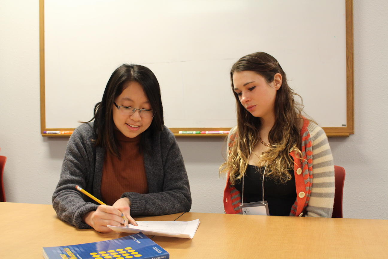 A tutor helps a student with a writing assignment.