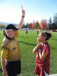Soccer team member receiving a red card from an umpire
