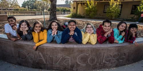 Students on the De Anza Sign (students-elbows-on-sign.jpg)