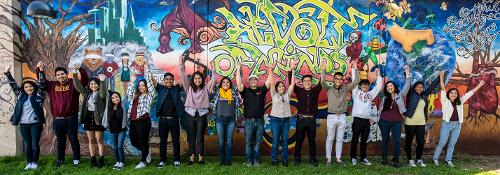 Students in front of the mural (students-hands-raised-mural.jpg)