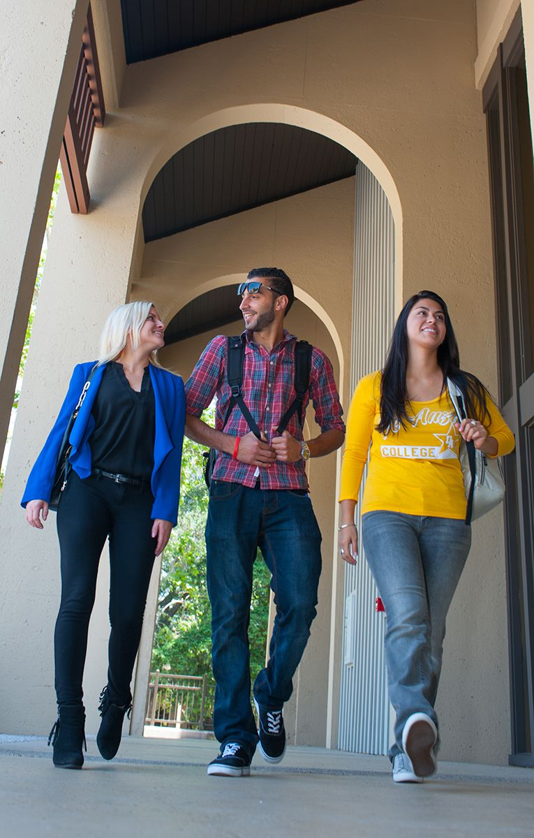 students walking under an archway