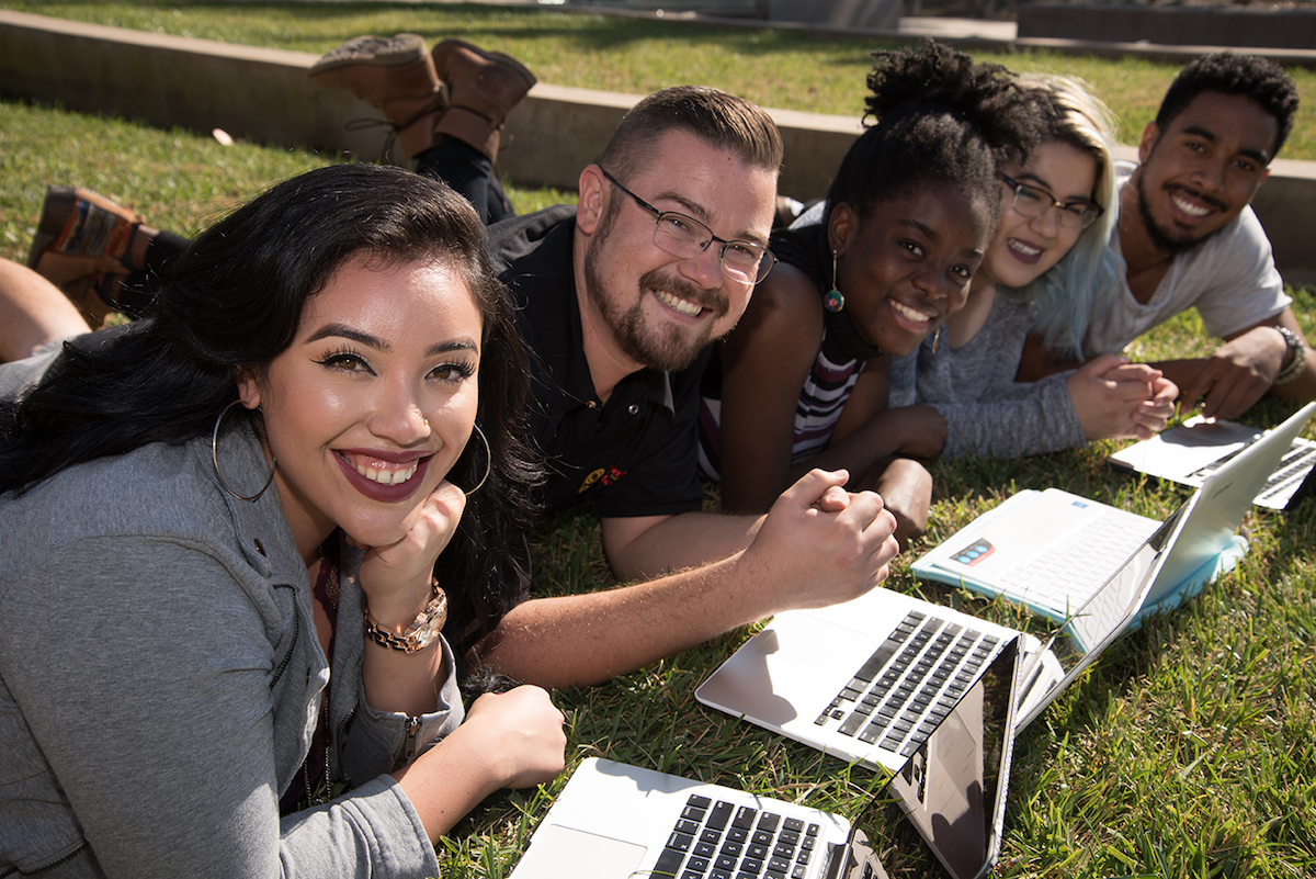 students on lawn with laptops