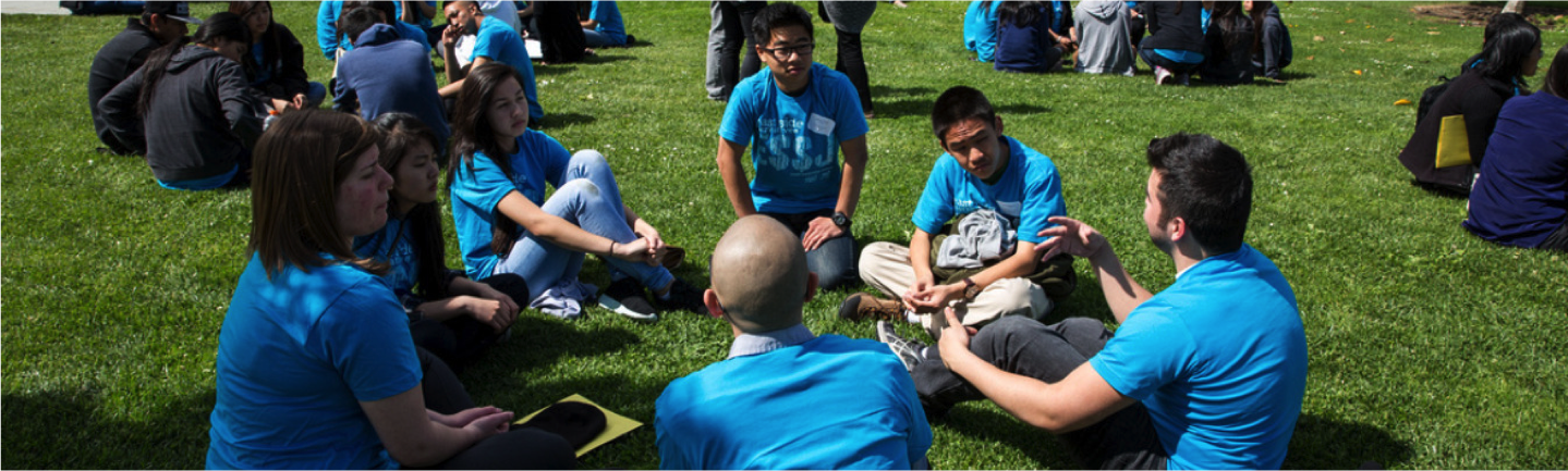 students sitting and talking on lawn