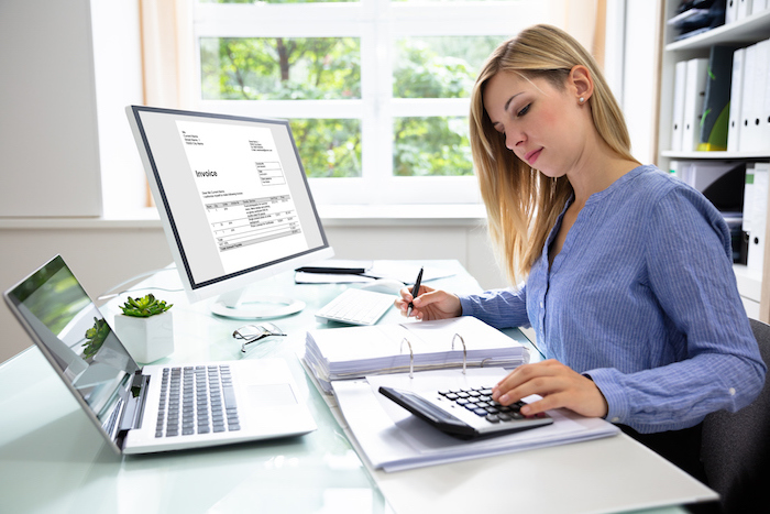 woman at desk with calculator