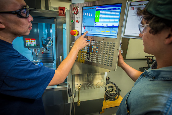 two students at CNC machine