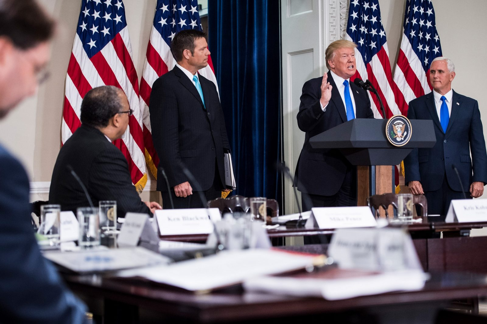 President Donald Trump, accompanied by Vice President Mike Pence and Kansas Secretary of State Kris Kobach, speaks to commissioners.