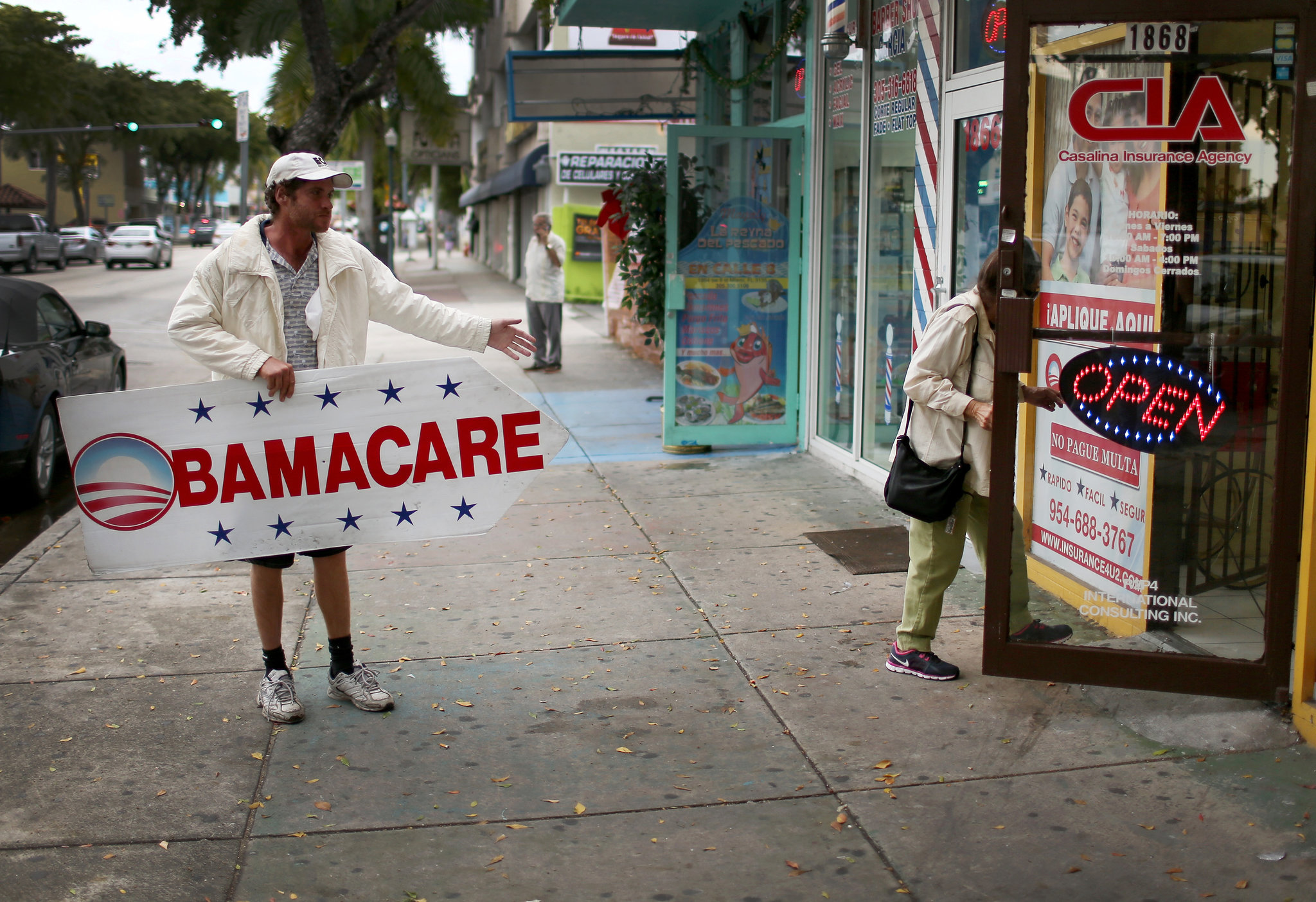 Man holding Obamacare sign points to insurance office