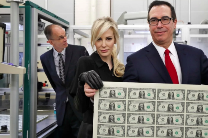 Treasury Secretary Steven Mnuchin, right, and his wife, Louise Linton, hold up a sheet of new $1 bills.
