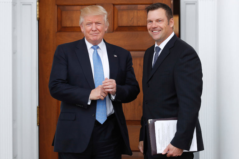 Kris W. Kobach standing with President Trump