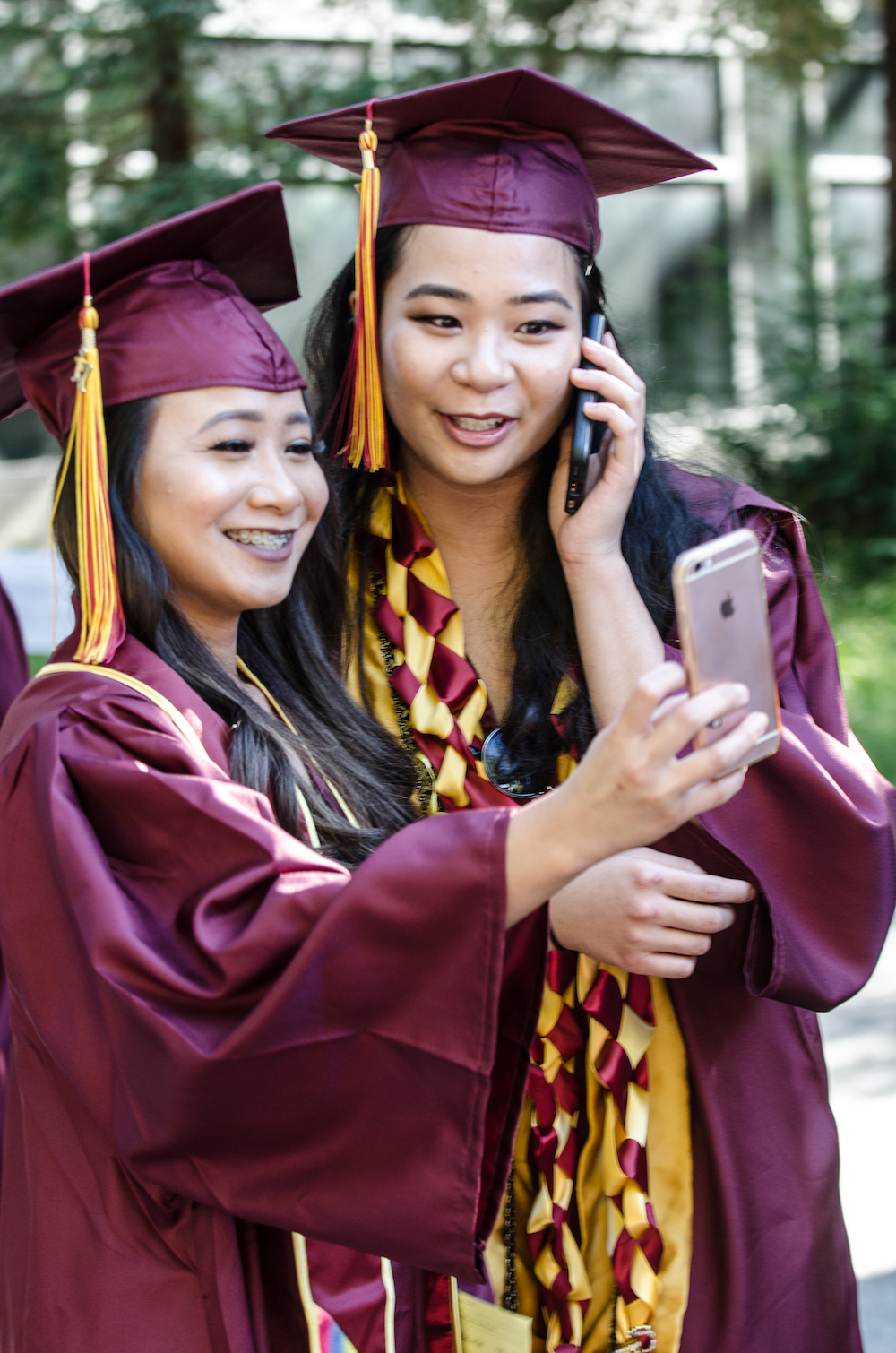 two graduates looking at phone