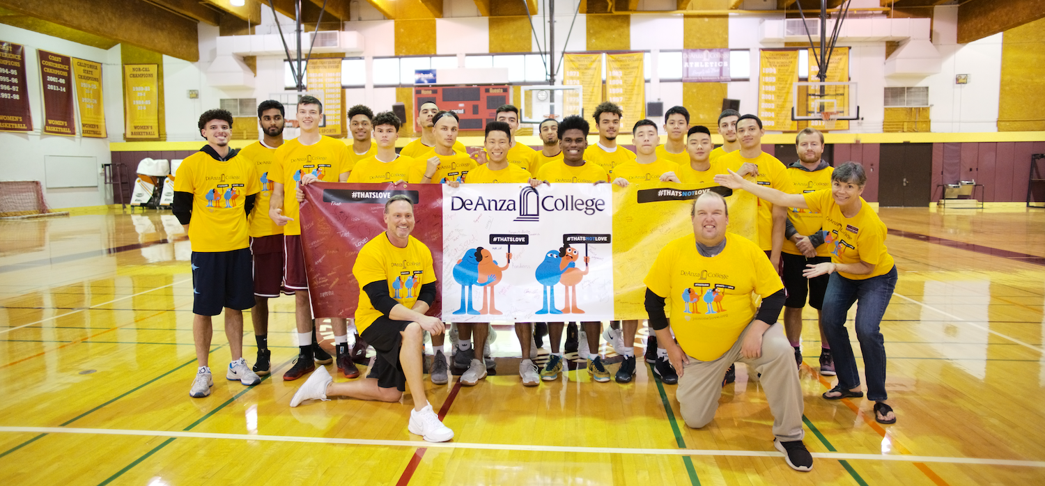 men's basketball team with banner against relationship violence