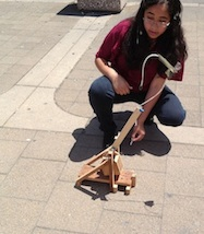 Female student launching her and her partners trebuchet.