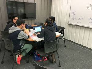 Image of students studying in a library group study room