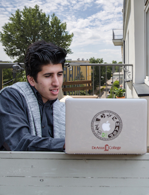 male student with laptop on balcony